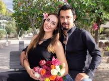 Het verhaal van de liefde Een man en een vrouw koesteren zitting op een bank in aard in een bloeiende tuin Met een boeket van blo stock afbeeldingen