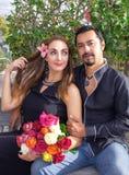 Het verhaal van de liefde Een man en een vrouw koesteren zitting op een bank in aard in een bloeiende tuin Met een boeket van blo royalty-vrije stock afbeeldingen