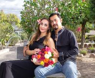 Het verhaal van de liefde Een man en een vrouw koesteren zitting op een bank in aard in een bloeiende tuin Met een boeket van blo stock afbeelding