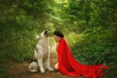 Het verhaal van een rood GLB met een scharlaken lange vliegende fladderende mantel, een donker-haired meisje behandelt haar gezic stock foto