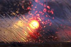 Het verkeer wordt door het windscherm van de auto bekeken in regen wordt behandeld die, mooie achtergrond van regen en lichten royalty-vrije stock afbeelding