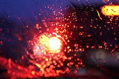 Het verkeer wordt door het windscherm van de auto bekeken in regen wordt behandeld die, mooie achtergrond van regen en lichten royalty-vrije stock foto