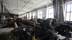 Het verlaten spinnen in fabriek met wind stock footage