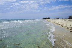 Het verlaten sprookjestrand met gouden zand, mooie hemel en turkoois water op de kusten van oceaan royalty-vrije stock afbeelding