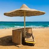 Het verlaten strand met wattled zonparaplu Stock Foto