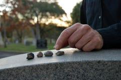 Het verlaten van kiezelstenen op grafsteen Stock Fotografie