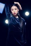 Het verleidelijke Aziatische vrouw stellen in avondjurk en diamantoorringen en het bekijken camera gebeurtenis met schijnwerpers Stock Foto's