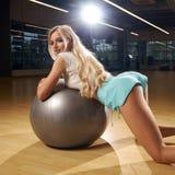 Het verleidelijke blonde vrouwelijke model stellen die op zilveren saldobal leunen stock afbeelding