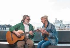 Het verliefde hogere paar ontspannen met gitaar en thee royalty-vrije stock foto's