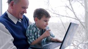 Het vermaak van gepensioneerdeinternet, kleinzoon met grootvader het spelen op computer in Internet-spel thuis stock videobeelden