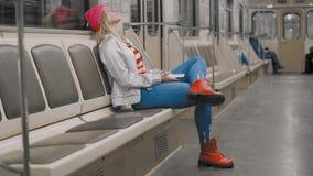 Het vermoeide aantrekkelijke blondemeisje luistert aan muziek en geeuwt op weg naar huis in de metro in ondergronds stock videobeelden