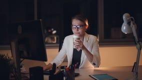Het vermoeide blonde in glazen en kostuum werkt aan computer laat bij nacht en het drinken meeneem vermoeid koffiegevoel en stock footage