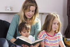 Het vermoeide boek van de moederlezing aan jonge geitjes stock foto