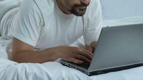 Het vermoeide freelancer werken aan oude laptop op huisbed, vermoeide overwerkte mens, spanning stock video
