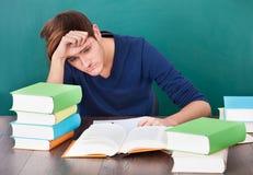 Het vermoeide jonge mens bestuderen stock afbeelding
