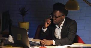 Het vermoeide jonge zwarte zakenman vallen in slaap voor het computerscherm, toen ontwaken en houdt bij het werken stock footage