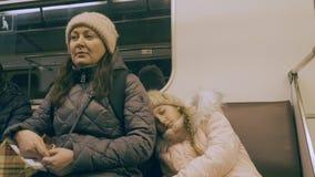 Het vermoeide mamma en van de slaapdochter drijven in metro trein in moderne stad stock video