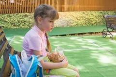Het vermoeide meisje in park zit op een bank met een pak koekjes in haar handen stock foto