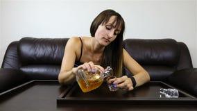 Het vermoeide meisje vult een glas met alcohol en valt op de lijst stock video