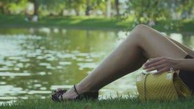 Het vermoeide meisje zit dichtbij de vijver en ontspant op groen gras stock videobeelden