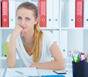 Het vermoeide meisje zit propped hoofd in zijn handen bij een bureau in het bureau Stock Foto's