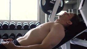 Het vermoeide mens ontspannen op bank na het doen van de oefening van de borstpers bij de gymnastiek stock video