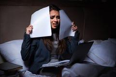 Het vermoeide onderneemster het werk overwerk thuis bij nacht stock fotografie