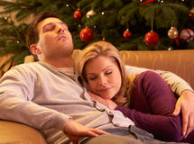 Het vermoeide Ontspannen van het Paar voor Kerstboom Royalty-vrije Stock Afbeeldingen