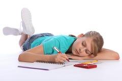 Het vermoeide schoolmeisje valt in slaap het doen math thuiswerk Stock Fotografie