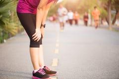 Het vermoeide Sportmeisje na het aanstoten of het lopen werkt in park uit Sport en gezondheidszorgconcept stock foto