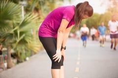 Het vermoeide Sportmeisje na het aanstoten of het lopen werkt in park uit Sport en gezondheidszorgconcept stock fotografie