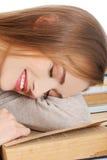 Het vermoeide vrouw slepping op boeken Stock Foto's