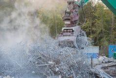 Het vernielingsgraafwerktuig scheurt van een gebouw stock foto