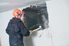 Het vernielingswerk en herschikking arbeider met voorhamer die muur vernietigen stock fotografie