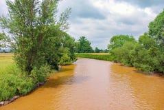 Het verontreinigde platteland van rivier oranje groene bomen royalty-vrije stock fotografie
