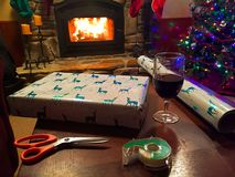 Het verpakken van een Kerstmisgift terwijl het genieten van van een brand en van een glas wijn Royalty-vrije Stock Foto