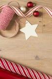 Het verpakkende document van de Kerstmisgift en lintenlevering op houten achtergrond stock afbeelding