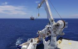 Het verplaatsen van lading tussen schepen bij bezig olieveld met gebruik van groot stock afbeelding