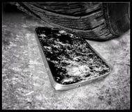 Het verpletteren van een smartphone met autoband royalty-vrije stock afbeeldingen