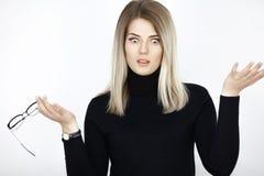 Het verraste jonge aantrekkelijke blonde spreidt haar wapens aan kant uit royalty-vrije stock foto
