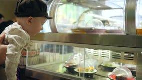 Het verraste jonge geitje in koffie kijkt op showcase met verschillende sushi bij het bewegen van platen stock videobeelden