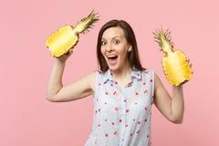 Het verraste jonge meisje in de zomer kleedt het houden van helft van de mond de open greep van vers rijp ananasfruit op roze stock foto