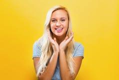 Het verraste jonge vrouw stellen op een stevige achtergrond Royalty-vrije Stock Afbeeldingen