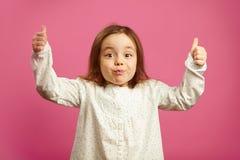 Het verraste meisje met opgeheven handen, toont duimen, heeft een overweldigd gezicht, drukt verrassing en vreugde op roze muur u stock foto's
