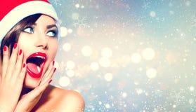 Het verraste meisje van Kerstmis Schoonheidsvrouw in Kerstman` s hoed stock fotografie