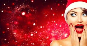 Het verraste meisje van Kerstmis Schoonheidsvrouw in Kerstman` s hoed stock afbeelding