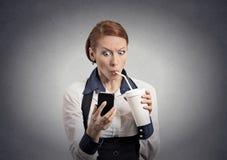 Het verraste nieuws van de vrouwenlezing op smartphone het drinken soda Stock Afbeeldingen
