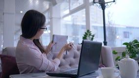 Het verre leren, de jonge vrouw die online op laptop apparaat communiceren en tonen blocnote met nota's zittend bij lijst in koff stock video