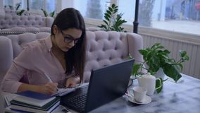 Het verre online leren, portret van gelukkige jonge vrouw in oogglazen schrijft nota's in notitieboekjezitting bij lijst met stock videobeelden
