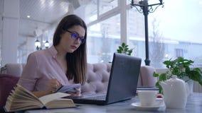 Het verre online leren, studente schrijft nota's in notitieboekje en gelezen boekzitting bij lijst met laptop stock footage